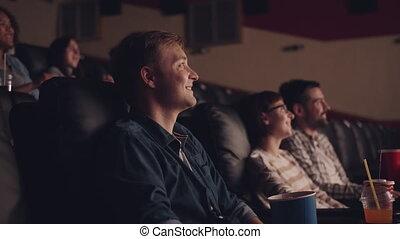 rire, jeune, vue, film regardant, côté, manger, pocorn, homme, cinéma