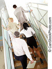 Rise - Back view of group of business people going upstairs...