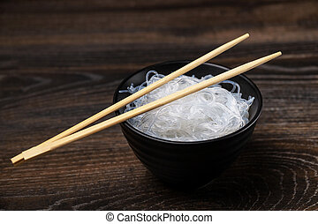 Rise noodles in black bowl on wooden background