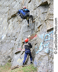 Rise on a rock - Alpinists climb on a mountain