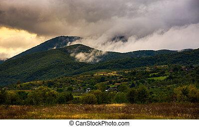rising clouds in mountainous countryside at menacing...