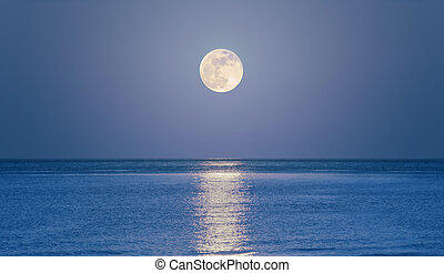 Rising moon on sea - Big full moon is rising above the sea ...