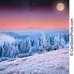 Rising moon over frosty winter mountains.