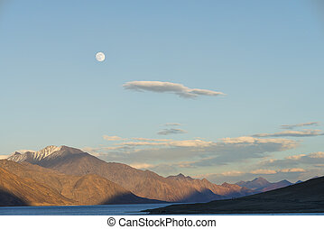 Rising moon over mountain and lake