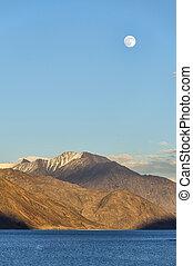 Rising moon over mountain lake