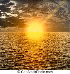 Rising sun on the horizon, dark sea, ocean