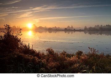 rising sun over wild lake during misty morning, Drenthe,...