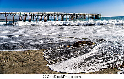 Rising Tide and Ocean Pier - Waves wash ashore beside the...