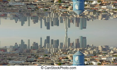 Rising up view of large city with skyline in background. Horizontal mirror post process effect. Abstract footage. Los Angeles, US. 4K.