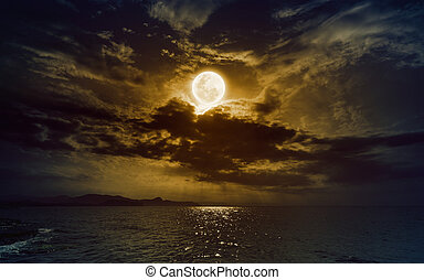 Rising yellow full moon in dark night sky with reflection in water