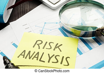 Risk analysis concept. Magnifying glass and business documents.