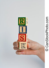 Risk concept with wooden pieces of a game forming the word Risk
