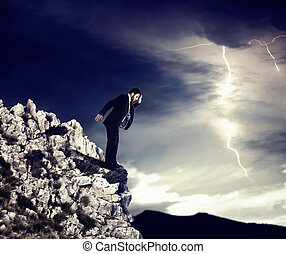 Risk - Businessman on the precipice with storm