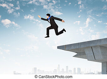 Risky business - Image of jumping businessman at the edge of...