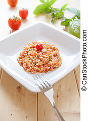 Risotto al pomodoro - Dish of tomatoes risotto on wood table