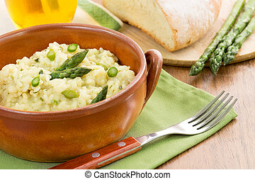 risotto with asparagus in a terracotta bowl over a green...