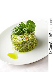 photo of delicious risotto with basil on white isolated background