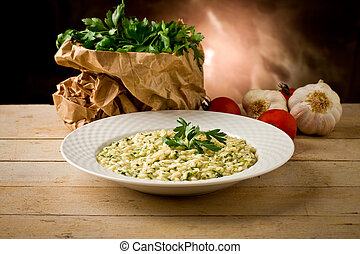 photo of delicious risotto dish with herbs on wooden table