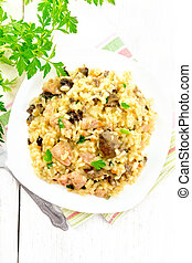 Risotto with mushrooms and chicken on wooden board top