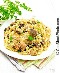 Risotto with mushrooms and chicken on wooden table