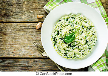 risotto with spinach on a dark wood background. tinting. ...