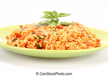 Risotto with tomatoes on a green plate decorated with basil
