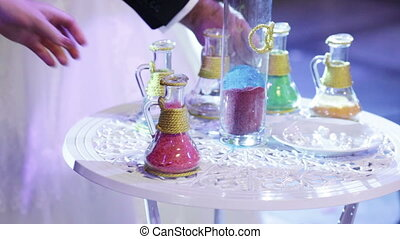 Rite Sand ceremony - Bride and groom are mixed multicolored...