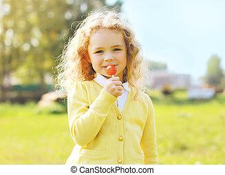 ritratto, carino, piccola ragazza, bambino, con, caramello, su, bastone