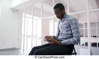 ritratto, di, americano africano, chi, lavori in corso, su, tavoletta, mentre, seduta, su, chair.