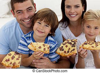 ritratto, di, famiglia felice, consumo pizza, in, soggiorno, insieme