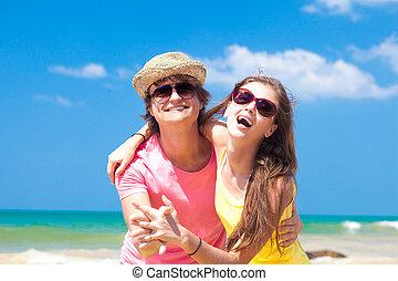 ritratto, di, felice, giovane coppia, in, occhiali da sole, sorridente, su, spiaggia