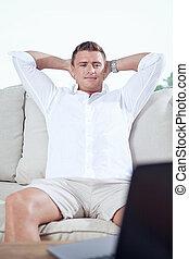 ritratto, di, giovane, sedere divano, con, laptop, in, casa estate, ambiente