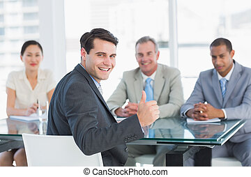 ritratto, di, un, esecutivo, gesturing, pollici, con, recruiters, durante, uno, intervista lavoro, a, ufficio
