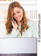 ritratto, di, uno, bello, giovane, sedere divano, e, usando computer portatile, a casa, comunicando telefono mobile