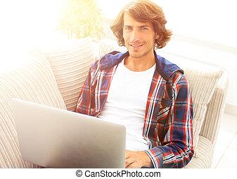 ritratto, di, uno, giovane, con, uno, laptop, sedendo sedia