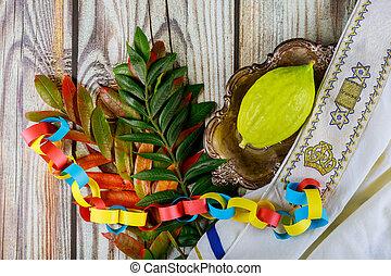 Ritual Jewish festival of Sukkot in the jewish religious symbol Etrog, lulav kippah and tallit praying book