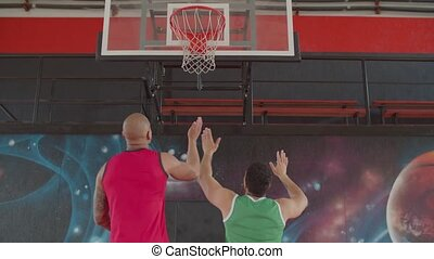 Athletic rival african american basketball players boxing out for better position while fighting for rebound during game. Two athletes jumping for capturing rebound on indoor basketball court.