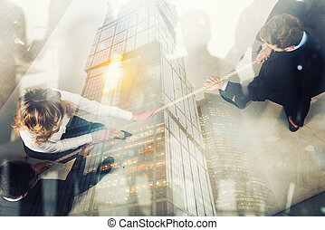 Rival business man and woman compete for the command by pulling the rope. Double exposure effect