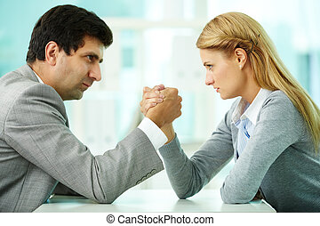 Rivalry - Man and woman in arm wrestling gesture on working...