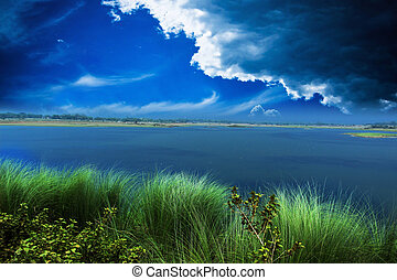 River and dark cloud with colorful green grass