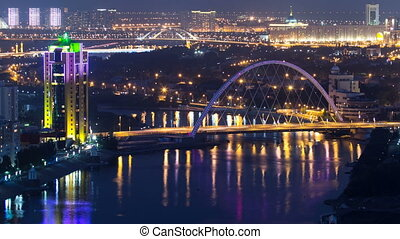 River and illuminated bridge reflected on water timelapse from rooftop at night in Astana. Kazakhstan capital