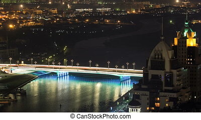 River and illuminated bridge timelapse from rooftop at night in Astana. Kazakhstan capital