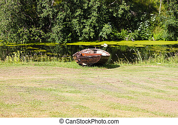 River and old rowing boat in green grass