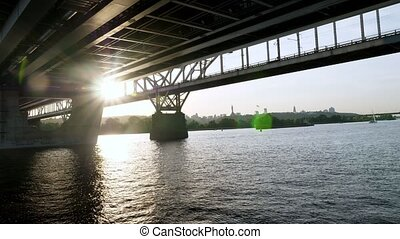 A river barge sails under the bridge over the Dnieper in Kiev. Urban summer landscape.