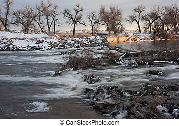 one of many dams on South Platte River in Colorado diverting water for farmland irrigation, ditch headgate (inlet), winter scenery