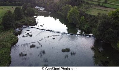 River Dobra in Croatia with small waterfalls. Drone recording.