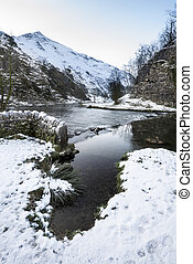 River flowing through snow covered Winter landscape in forest valley