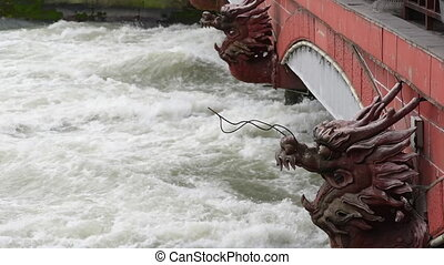 River flowing under a bridge with red dragon head sculptures...