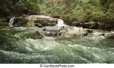 River roars and hisses as it tumbles over and around rocks, flowing through an exotic, jungle wilderness near Chiang Mai, Thailand. FullHD 1080p video