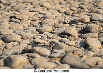 River gravel in the sun during the day.